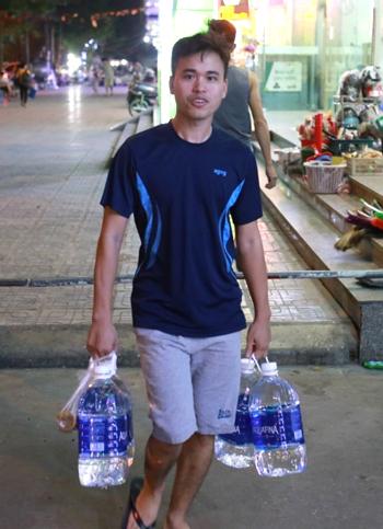 Anh Hà Quốc Tú (chung cư HH2C Linh Đàm) mua nước đóng chai về nấu ăn. Ảnh: Tất Định.