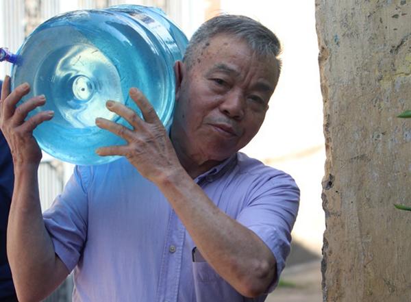 Ông Đinh Tiến Dũng mua nước đóng bình về nấu ăn. Ảnh: Võ Hải.