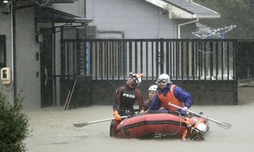 Nhân viên cứu hộ đi thuyền cao su tìm kiếm người còn mắc kẹt trong những ngôi nhà ở thành phố Ise, tỉnh Mie. Ảnh: Reuters.