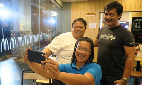 Ca sĩ Sonny Parsons (áo đen), thành viên ban nhạc Hagibis, chụp ảnh cùng fan tại một quán ăn ở Manila, Philippines hôm 11/10. Ảnh: Reuters