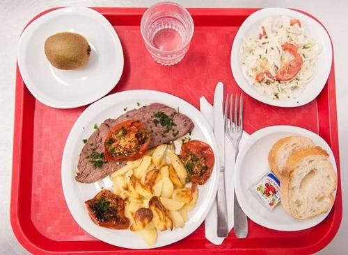 Một trường học ở Lyon bữa trưa gồm salad bắp cải và cà chua, một quả kiwi, bánh mì cắt lát ăn kèm pho mát, món chính là thịt bò nướng cùng khoai tây, cà chua và thảo mộc tươi.