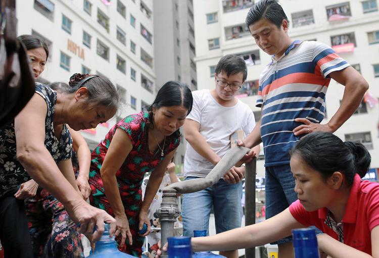 Cư dân tổ hợp chung cư HH Linh Đàm phải tự bỏ kinh phí mua nước sạch bằng xe téc dùng cho sinh hoạt. Ảnh: Tất Định.