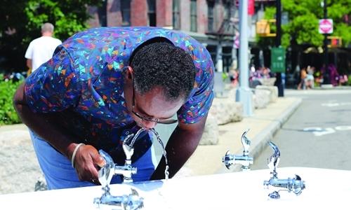 Một người đàn ông uống nước từ vòi công cộng ở New York. Ảnh: