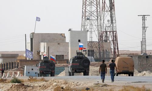 Các phương tiện treo cờ Nga và Syria ở gần thị trấn Manbij, phía bắc Syria hôm nay. Ảnh: Reuters.