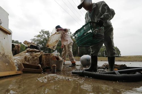 Vợ chồng ông Saito dọn dẹp ở khoảng sân trước nhà sau khi nước rút hôm 14/10. Ảnh: AP.