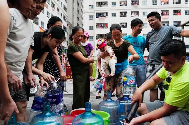 Cư dân HH Linh Đàm xếp hàng lấy nước sạch từ xe téc chiều 14/10. Ảnh: Ngọc Thành.