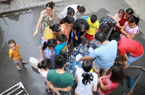 Cư dân tổ hợp chung cư HH Linh Đàm lấy nước sinh hoạt từ xe téc do những ngày qua nước sông Đà không đảm bảo chất lượng. Ảnh: Tất Định