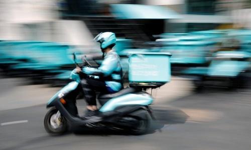Một nhân viên giao hàng của Baedal Minjok lái xe máy trên đường phố Seoul, Hàn Quốc, hồi tháng 6. Ảnh: Reuters.
