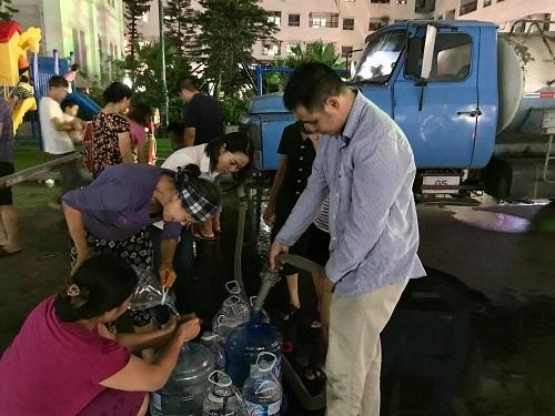 Người dân nhận nước tại các xe téc lưu động. Ảnh: Gia Chính