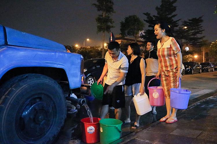 Người dân xếp hàng lấy nước sạch trong đêm. Ảnh: Giang Huy.