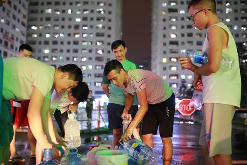 Người dân chung cư HH Linh Đàm lấy nước sạch từ xe téc lúc 19h30 ngày 16/10. Ảnh: Tất Định