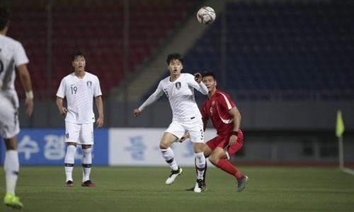 Một pha tranh bóng giữa cầu thủ Hàn Quốc (áo trắng) và cầu thủ Triều Tiên trong trận đấu ngày 15/10. Ảnh: KFA.