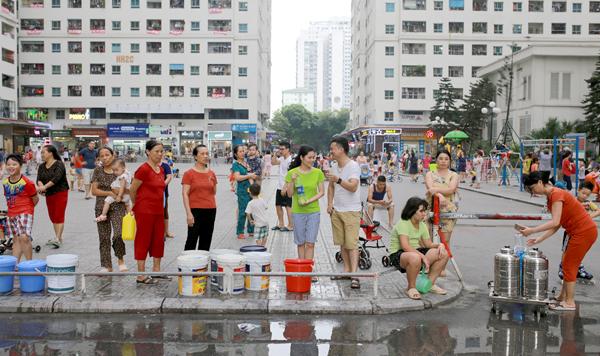 Người dân nhiều khu đô thị ở Hà Nội xếp hàng chờ lấy nước từ xe téc. Ảnh: Tất Định.