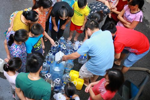 Một tuần qua, hàng nghìn hộ dân khu vực Tây Nam Hà Nộiphải đi xách nước từ xe tec, mua nước đóng chai nấu ăn vì nước sạch nhiễm Styren. Ảnh: Tất Định