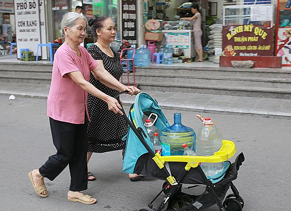 Người dân khu đô thị Linh Đàm chở nước bằng xe nôi. Ảnh: Tất Định.