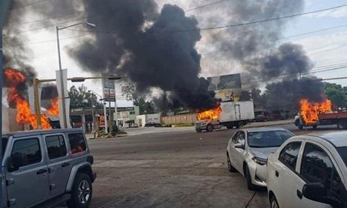 Những chiếc xe tải đangbốc cháy chặn một trong những conđường chính ra khỏi thành phố Ciliacán, bang Sinaloa, Mexico, hôm 17/10. Ảnh: Mirror.