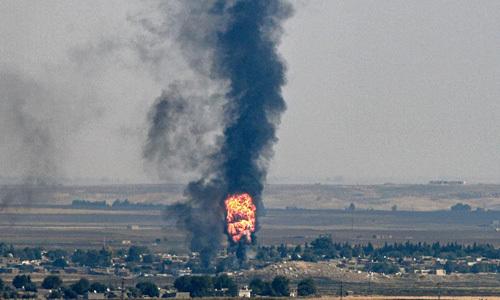 Lửa và khói bốc lên từ thị trấn Ras al-Ain, Syria sát biên giới với Thổ Nhĩ Kỳ hôm 17/10. Ảnh: AFP.