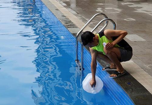 Người dân múc nước bể bơi để dùng cho sinh hoạt. Ảnh: Hà Trang.
