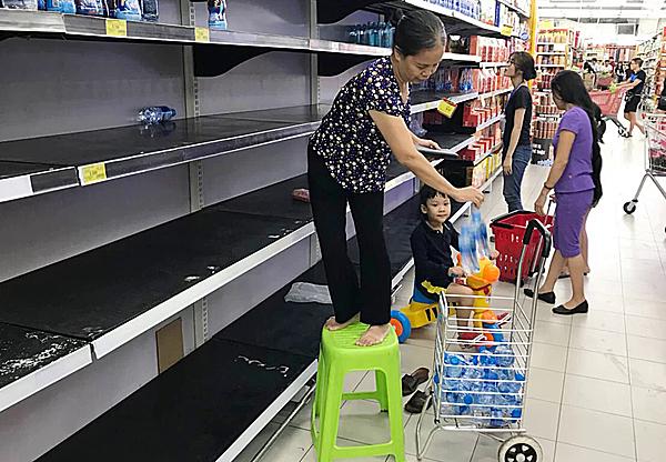 Nước đóng chai bị vét sạch trên kệ hàng của một siêu thị lớn tối16/10, khi nhà máySông Đà ngừng cấp nước để xúc rửa ống.Ảnh: Ngọc Thành.
