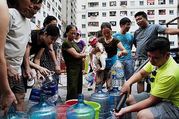 Người dân chung cư HH Linh Đàmxếp hàngchờ lấy nước sạch về dùng. Ảnh: Ngọc Thành.