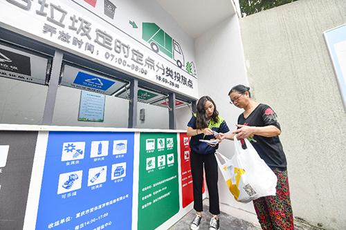 Giám sát viên hướng dẫn một người dân phân loại rác tại thành phố Trùng Khánh, tây nam Trung Quốc hồi tháng 6. Ảnh: Xinhua