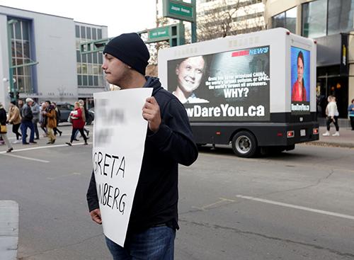 Người ủng hộ ngành dầu khí cầm biểu ngữ phản đối Greta Thunberg trước xe tải ở thành phố Edmonton, Canada hôm 18/10. Ảnh: Reuters