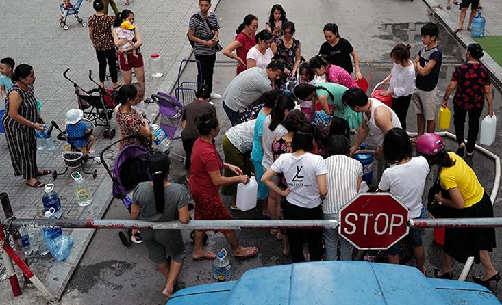 Người dân khu chung cư HH Linh Đàm xếp hàng lấy nước sạch từ xe tec, chiều 16/10. Ảnh: Giang Huy.