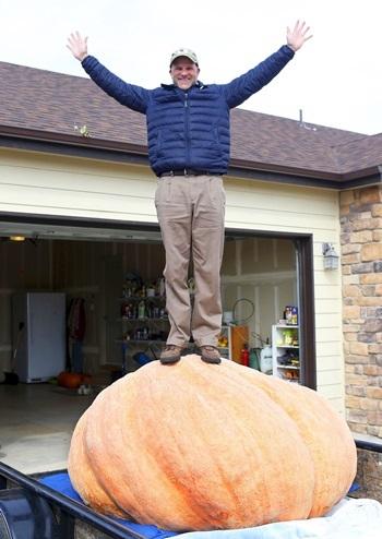 Ông Corbi chụp ảnh cùng quả bí ngô khổng lồ nặng 676 kg được thu hoạch hôm 16/10. Ảnh: AP.