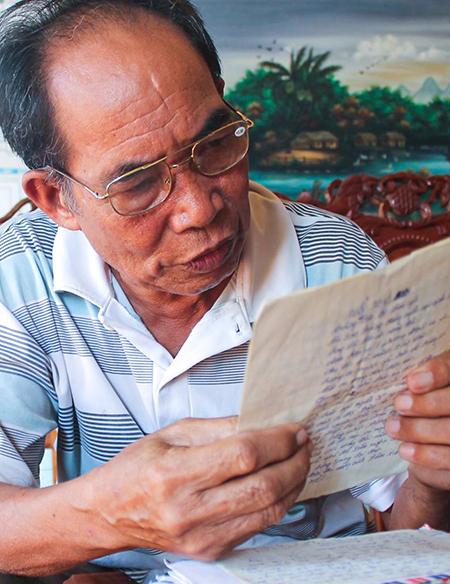 Ông Vũ Quang Dương, cha liệt sĩ Vũ Quang Chương đọc lại thư con gửi khi công tác ở tiểu đoàn DK1. Ảnh: Trần Hóa.