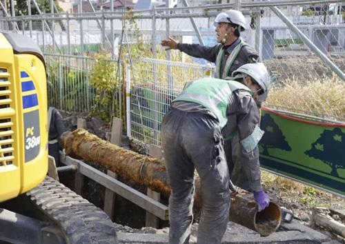 Các công nhân thay thế một đoạn ống nước rỉ sét tại thành phố Fuchu, phía tây Tokyo, Nhật Bản hồi tháng 11/2018. Ảnh: Kyodo.