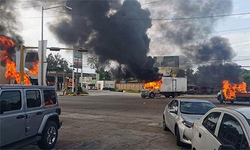 Những chiếc xe tải bị đốt để chặn đường trong trận đấu súng giữa lực lượng an ninh Mexico và thành viên băng đảng ma túy tại Culiacan, bang Sinaloa ngày 17/10. Ảnh: LAT.