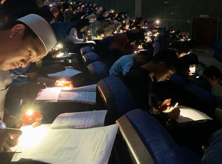 Do mất điện, sinh viên ngành Luật, Đại học Islam Antarabangsa Malaysia phải làm bài thi trong bóng tối. Ảnh: Mohd Ilhamy Mohd Nahzeri.