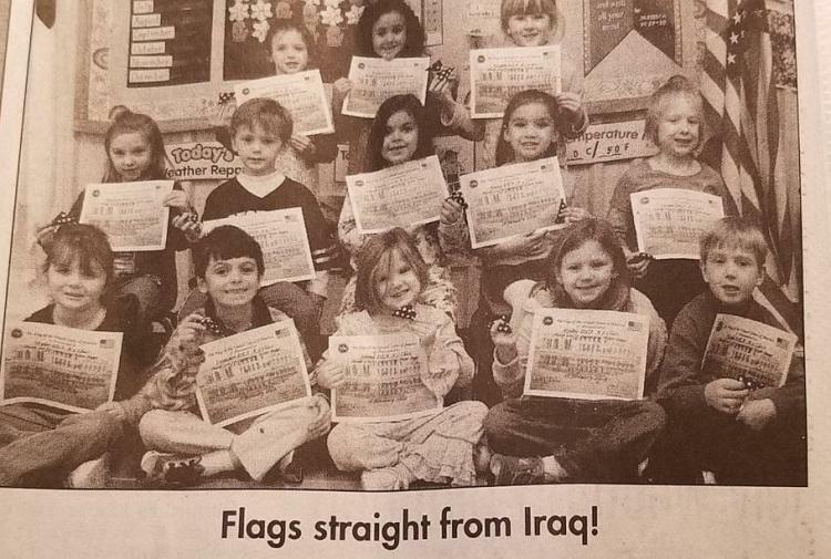Các học sinh của lớp mầm non K5 chụp cùng với những lá cờ Buggs gửi về từ Iraq. Ảnh: David Emanuel Academy