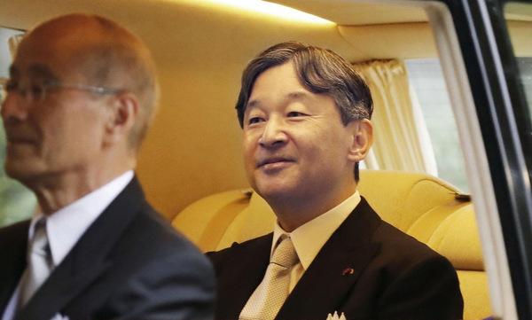 Nhật hoàng (phải) ngồi ôtô đến cung điện trước buổi lễ. Ảnh: Kyodo.