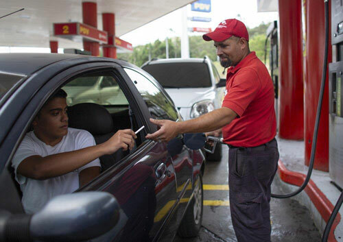 Leowaldo Sanchez poses with food items he was paid with by motorists: a bottle of cooking oil, a kilogram if rice and a package of corn flour, as he works at the pump in San Antonio de los Altos on the outskirts of Caracas