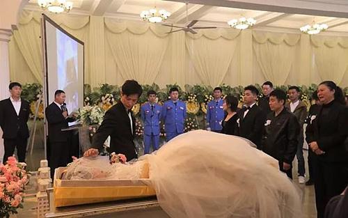 Chú rể Xu Shinan cạnh thi thể vợ trong tang lễ cũng là đám cưới của hai người hôm 19/10. Ảnh:  Dailian Evening News