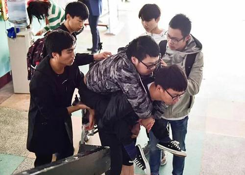 Li được các bạn cùng lớp cõng lên phòng học trên tầng 5. Ảnh:Li Shenhan/China daily