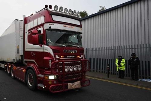 Hai cảnh sát cúi đầu khi xe container chở thi thể các nạn nhân rời khỏi hiện trường ở cảng Purfleet, hạt Essex hôm 24/10. Ảnh: AFP.
