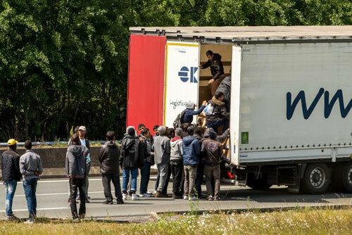 Người di cư chui vào thùng xe tải trên đường cao tốc gần Calais, Pháp năm 2015. Ảnh: AFP.