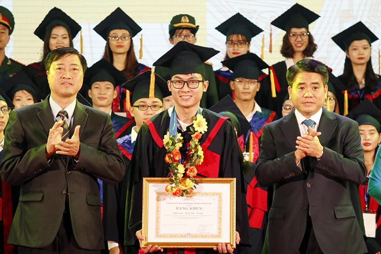 Chủ tịch UBNDTPHà Nội Nguyễn Đức Chung (bên phải) tặng bằng khen cho các thủ khoa xuất sắc. Ảnh: Thanh Hằng.