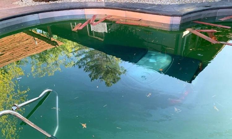 Ôtô chìm hoàn toàn dưới nước trong bể bơi có độ sâu khoảng 2,4 m.