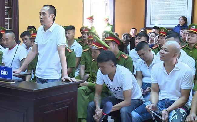 Tuấn Thần Đèn (đứng) và các bị cáo tại phiên xử sơ thẩm hôm nay. Ảnh: Lam Sơn.