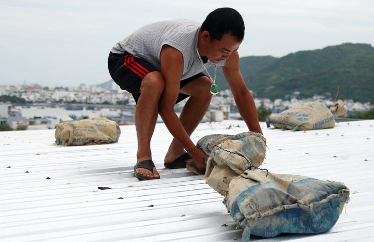 Anh Trần Ngọc Vinh, 39 tuổi, đang chằng chống nhà ở TP Nha Trang. Ảnh: Xuân Ngọc.