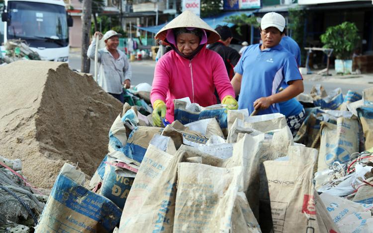 Người dân TP Nha Trang tất bật xúc cát chằng chống nhà. Ảnh: Xuân Ngọc.