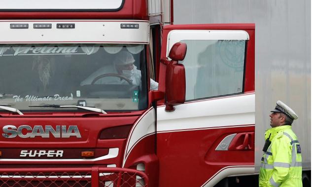 Cảnh sát và nhân viên pháp y di chuyển xe container chở 39 thi thể tại khu công nghiệp ở hạt Essex, Anh hôm 23/10. Ảnh: Reuters