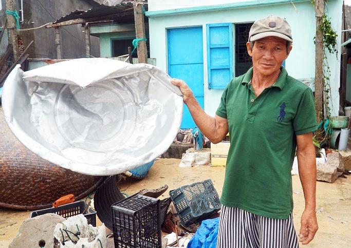 Ông Nguyễn Văn Cho ở xã Nhơn Hải, TP Quy Nhơn cầm chiếc thau inox bị sóng do bão Matmo đánh móp méo, chiều 31/10. Ảnh: Phạm Linh.
