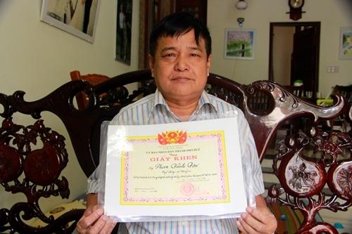 Phan Đình Đơn với tấm bằng khen được tặng 20 năm về trước. Ảnh: Võ Thạnh