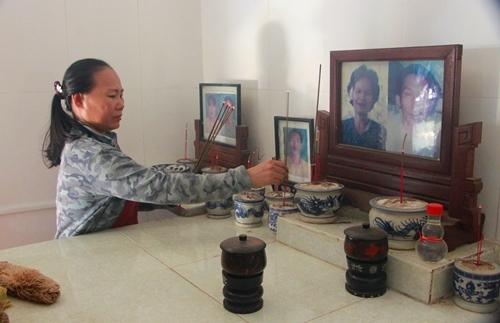 Bà Hương thắp hương cho 12 người thân chết trong lũ 1999. Ảnh: Võ Thạnh