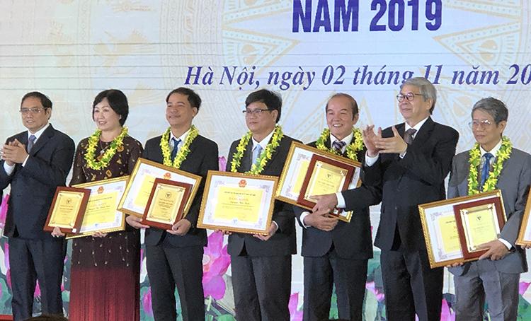 Ông Phạm Minh Chính, Trưởng Ban tổ chức Trung ương (bìa trái) và GS Đặng Vũ Minh trao bằng khen và biểu trưng cho các trí thức.