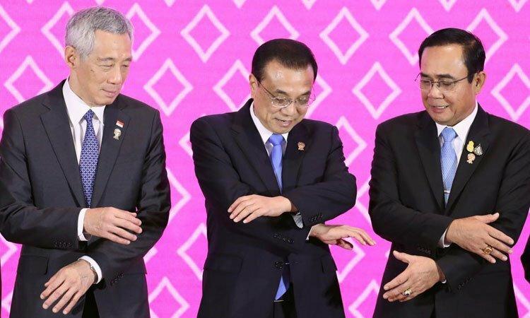 Thủ tướng Trung Quốc Lý Khắc Cường (giữa) bắt tay Thủ tướng Singapore Lý Hiển Long (trái) và người đồng cấp Thái LanPrayut Chan-ochatại Hội nghị Cấp cao ASEAN 35 tại Bangkok, Thái Lan hôm nay. Ảnh:Reuters.